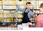 Купить «Seller assisting woman in choosing door hinges», фото № 33838741, снято 5 апреля 2017 г. (c) Яков Филимонов / Фотобанк Лори