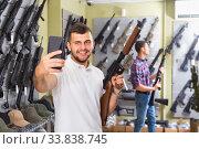 Купить «Male customer is taking selfie on phone with air gun», фото № 33838745, снято 4 июля 2017 г. (c) Яков Филимонов / Фотобанк Лори