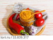 Vegetable caviar, diet puree of pumpkin and zucchini bright orange with pepper, tomatoes, garlic and spices in a glass jar. Vegetarian food, healthy nutrition. Canning homemade crop. Стоковое фото, фотограф Светлана Евграфова / Фотобанк Лори