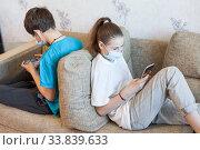 Children are in online interactions during coronavirus pandemic, kids wearing safety masks staying at home. Стоковое фото, фотограф Кекяляйнен Андрей / Фотобанк Лори