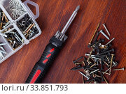Купить «Multifunctional screwdriver among various self-tapping screws», фото № 33851793, снято 13 июля 2020 г. (c) Яков Филимонов / Фотобанк Лори