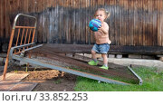 Купить «Tranquil small girl playing ball in yard in daytime», видеоролик № 33852253, снято 11 мая 2020 г. (c) Ekaterina Demidova / Фотобанк Лори