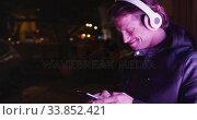 Caucasian hooded male wearing headphones, smiling, lying on the wall, in the evening. Стоковое видео, агентство Wavebreak Media / Фотобанк Лори