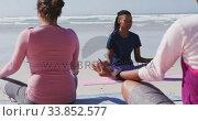 Купить «Multi-ethnic group of women doing yoga on the beach and blue sky background», видеоролик № 33852577, снято 15 октября 2019 г. (c) Wavebreak Media / Фотобанк Лори