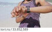 Mixed race woman looking at her smartwatch on the beach and blue sky background. Стоковое видео, агентство Wavebreak Media / Фотобанк Лори