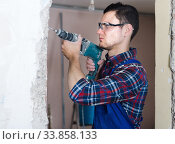 Купить «Builder handyman with electric drill indoors», фото № 33858133, снято 21 мая 2017 г. (c) Яков Филимонов / Фотобанк Лори