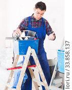 Купить «Young attentive builder handyman choosing tool in toolbox», фото № 33858137, снято 21 мая 2017 г. (c) Яков Филимонов / Фотобанк Лори