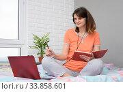 Счастливая студентка в пижаме дома сидя на кровати в спальне проходит курс интерактивного онлайн обучения. Стоковое фото, фотограф Иванов Алексей / Фотобанк Лори