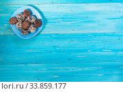 Домашние конфеты из сушеных фиников с орехами и какао на синем деревянном столе. Десерт. Стоковое фото, фотограф Наталья Гармашева / Фотобанк Лори