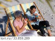 Купить «Senior Caucasian couple sitting on deck chairs at the beach.», фото № 33859289, снято 25 февраля 2020 г. (c) Wavebreak Media / Фотобанк Лори