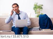 Купить «Young male employee working from house», фото № 33871513, снято 30 октября 2019 г. (c) Elnur / Фотобанк Лори