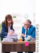 Купить «Two employees and excessive work in the office», фото № 33872413, снято 15 октября 2019 г. (c) Elnur / Фотобанк Лори