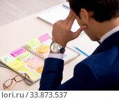 Купить «Young handsome employee planning his work activity», фото № 33873537, снято 1 августа 2018 г. (c) Elnur / Фотобанк Лори