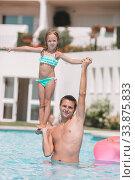 Family of mom and little daughter enjoying summer vacation in luxury swimming pool. Стоковое фото, фотограф Дмитрий Травников / Фотобанк Лори