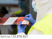 Купить «healthcare worker sealing door with caution tape», фото № 33876821, снято 24 апреля 2020 г. (c) Syda Productions / Фотобанк Лори