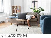 Купить «bored woman with laptop lying on sofa at home», фото № 33876969, снято 15 апреля 2020 г. (c) Syda Productions / Фотобанк Лори