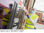 Купить «healthcare worker sealing door with caution tape», фото № 33877337, снято 24 апреля 2020 г. (c) Syda Productions / Фотобанк Лори