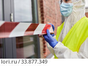 Купить «healthcare worker sealing door with caution tape», фото № 33877349, снято 24 апреля 2020 г. (c) Syda Productions / Фотобанк Лори