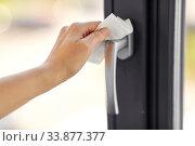 Купить «woman cleaning window handle with wet wipe», фото № 33877377, снято 24 апреля 2020 г. (c) Syda Productions / Фотобанк Лори