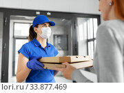 Купить «delivery girl in mask giving pizza boxes to woman», фото № 33877469, снято 15 апреля 2020 г. (c) Syda Productions / Фотобанк Лори