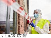 Купить «healthcare worker sealing door with caution tape», фото № 33877481, снято 24 апреля 2020 г. (c) Syda Productions / Фотобанк Лори