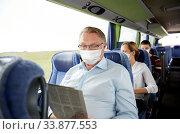 senior man in mask reading newspaper in travel bus. Стоковое фото, фотограф Syda Productions / Фотобанк Лори