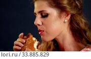 Купить «Girl eating hamburger. Fast Food burger of woman flirty nibble», видеоролик № 33885829, снято 28 декабря 2019 г. (c) Gennadiy Poznyakov / Фотобанк Лори