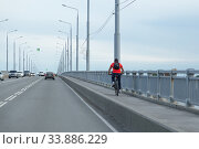 Saratov region, Russia - 05/22/2020: An adult man on a street in the summer afternoon rides a bicycle over the Saratov bridge Engels city. Active healthy lifestyle, outdoor sport hobby in urban space. Редакционное фото, фотограф Светлана Евграфова / Фотобанк Лори