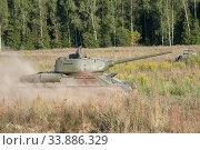 Советский средний танк времен Великой Отечественной войны Т-34-85 движется по полю в пыли (2018 год). Редакционное фото, фотограф Малышев Андрей / Фотобанк Лори