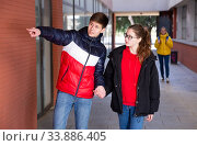 Teen boy pointing at something to girlfriend. Стоковое фото, фотограф Яков Филимонов / Фотобанк Лори