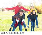 Laughing teenage girls riding piggy-back on boys. Стоковое фото, фотограф Яков Филимонов / Фотобанк Лори