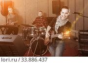 Купить «Attractive female soloist playing guitar and singing with her mu», фото № 33886437, снято 26 октября 2018 г. (c) Яков Филимонов / Фотобанк Лори