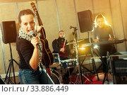 Купить «Jolly woman guitar player and singer with band», фото № 33886449, снято 26 октября 2018 г. (c) Яков Филимонов / Фотобанк Лори