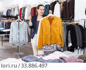 Woman demonstrating clothes on hangers in boutique. Стоковое фото, фотограф Яков Филимонов / Фотобанк Лори