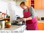 Mature woman housewife during cooking soup at her kitchen. Стоковое фото, фотограф Яков Филимонов / Фотобанк Лори