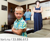 Unhappy small boy sitting at sofa during his parents quarrelling. Стоковое фото, фотограф Яков Филимонов / Фотобанк Лори