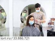 Man doing haircut for woman in salon using face masks. Стоковое фото, фотограф Яков Филимонов / Фотобанк Лори