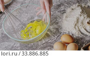 Купить «Woman's hands start to whip fresh natural eggs in a glass bowl by whisk for preparation homemade cake on a table with flour an raw eggs. Slow motion, Full HD video, 240fps, 1080p.», видеоролик № 33886885, снято 2 июля 2020 г. (c) Ярослав Данильченко / Фотобанк Лори