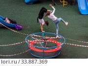 Купить «Девочки играют на закрытой властями города для посещения детской площадке около жилого дома в городе Москве во время эпидемии коронавируса COVID-19 в России», фото № 33887369, снято 25 мая 2020 г. (c) Николай Винокуров / Фотобанк Лори