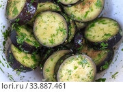 in a bowl, raw, struck eggplant in a marinade with herbs, dill in a rustic natural form. Preparation for grilling. View from above. Стоковое фото, фотограф Tetiana Chugunova / Фотобанк Лори