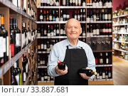 Senior male vintner giving recommendation about purchase wine in his wine house. Стоковое фото, фотограф Яков Филимонов / Фотобанк Лори