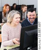 Middle aged man helping woman to use computer. Стоковое фото, фотограф Яков Филимонов / Фотобанк Лори