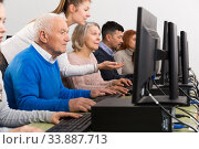 Young female teacher helping mature people to use computer. Стоковое фото, фотограф Яков Филимонов / Фотобанк Лори