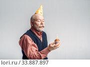 Купить «Smiling elderly man in cap shows cake with candle», фото № 33887897, снято 7 февраля 2020 г. (c) Tryapitsyn Sergiy / Фотобанк Лори