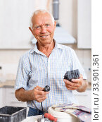 Купить «Senior man working on apartment overhauls», фото № 33901361, снято 19 июня 2018 г. (c) Яков Филимонов / Фотобанк Лори