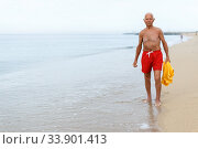 Купить «Joyful man in beachwear resting near ocean», фото № 33901413, снято 16 июня 2018 г. (c) Яков Филимонов / Фотобанк Лори