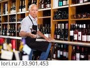 Купить «Confident elderly male owner of wine shop taking wine bottle from shelf rack and proffering to buy», фото № 33901453, снято 8 мая 2019 г. (c) Яков Филимонов / Фотобанк Лори