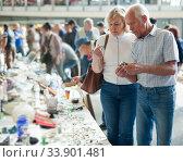 Elderly couple choose things on street market. Стоковое фото, фотограф Яков Филимонов / Фотобанк Лори