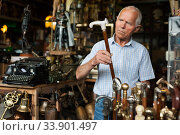 Elderly man chooses rare walking stick at street market. Стоковое фото, фотограф Яков Филимонов / Фотобанк Лори