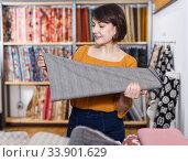 Купить «Happy woman choosing textiles», фото № 33901629, снято 7 февраля 2019 г. (c) Яков Филимонов / Фотобанк Лори